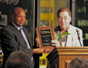 Gilbert arap Bor from Kenya being presented the 2011 Kleckner Trade & Technology Advancement Award by Dean Kleckner, GFN Chairman Emeritus.